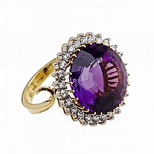 18k Yellow And White Gold Cocktail Ring, set with a large, round fancy cut amethyst encircled by 26 brilliant cut diamonds (approx. 1.00ct.t.w.)