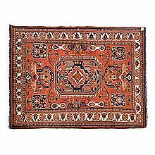 AN AFGHAN RUG, MODERN the madder-red field with a large blue octagon gul, a