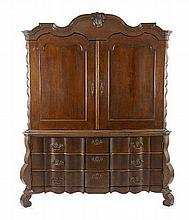 A DUTCH OAK ARMOIRE, 18TH CENTURY the gabled top centred by a leaf-carved k