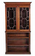 AN EDWARDIAN MAHOGANY AND INLAID BOOKCASE the moulded outswept cornice abov