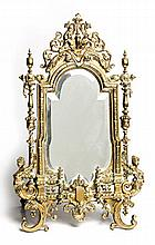 A VICTORIAN CAST-BRASS STANDING MIRROR the shaped and bevelled plate within