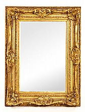 A GILTWOOD MIRROR, 19TH CENTURY the rectangular bevelled plate within a con
