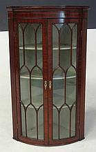 A GEORGE III MAHOGANY BOWFRONTED CORNER CABINET the outswept pediment above