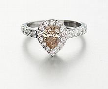 A DIAMOND RING centred with a cognac-coloured, pear-shaped diamond weighing