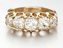A VICTORIAN DIAMOND RING centred with a row of five old-cut diamonds, gradu