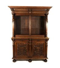 AN OAK BOOKCASE, 19TH CENTURY in two parts, the outswept pediment above two