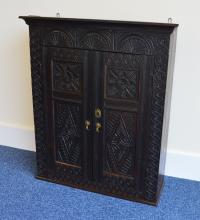 An oak carved wall cabinet with fitted interior an