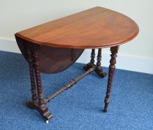 A small mahogany drop leaf Sutherland table on tur