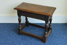 A reproduction oak joint stool with carved frieze,