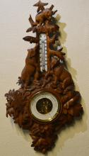 A good carved barometer mounted with numerous leav