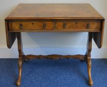 A walnut double drawer writing table on reeded sup