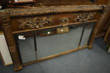 A gilt overmantle mirror decorated with flowers an