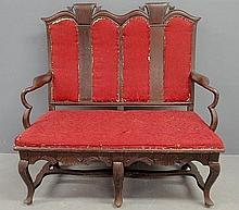 Dutch walnut settee, probably 18th c., with finely carved arms, cabriole legs all joined by a flat stretcher base. 46