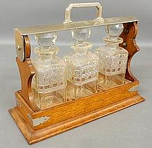 Travel decanter set, c.1900, with three cut glass bottles set in an oak and metal carrying case. Lacking key. 13