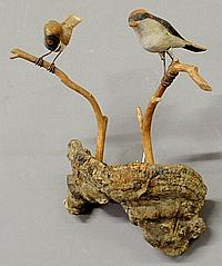 Two folk art carved and paint decorated birds, c.1930, perched on a tree mushroom. 12