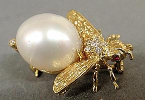 Ladies 18k gold bee pin with a mobé pearl body, ruby eyes and 6 small round brilliant cut diamonds between the wings, marked