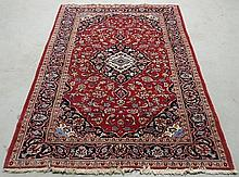 Kashan center hall oriental carpet with a red field, center medallion and overall floral patterns. 6'x9'