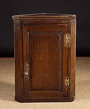 An 18th Century Oak Hanging Corner Cupboard.  The fielded panel door hung on brass H-form hinges fla