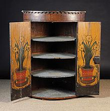 A Late 18th Century Oak Bow-front Hanging Corner Cupboard.  The hinged doors edged in mahogany cross