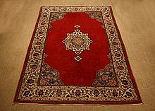 A Wool Carpet. The vibrant red ground centred by a