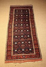 A Beluchi Wool Runner. Set on a red ground with