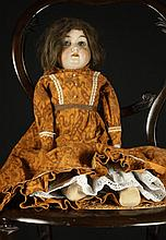 A Bisque Headed Doll with blue glass sleep eyes,