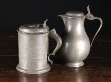 Two Antique Pewter Pieces: A Dutch Pewter Spouted Flagon of baluster form with hinged lid, 9½ ins (24 cms) in height. A 19th Century Swedish Pewter Tankard with wriggle work decoration and an inset coin of King Oscar to the lid, mark of IM Pohlammer, Gothenburg, Circa 1850, 8 ins (20 cms) in height.