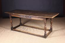 A Fine Joined Oak Refectory Table dated 1703. The planked top with cleated ends above run moulded rails; the front rail carved with the initials RA and date flanking a central daisy wheel in a recessed nail-pitted panel. Standing on decoratively turned legs united by peripheral stretchers, 28½ ins (72 cms) high, 75 ins x 28 ins (191 cm x 71 cms).