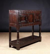A 17th Century Oak Livery Cupboard having two panel doors flanking a centre panel decorated with punchworked lozenge motifs and divided by split spindle appliqués, The cupboard raised on turned front legs and rear stiles leading down to a pot shelf below on nulled base rails, 46½ ins (118 cms) high, 49 ins (124.5 cms) wide, 16 ins (41 cms) deep.