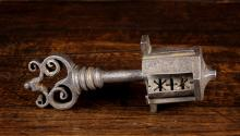 A Late 16th/17th Century Lock & Key with scroll work handle, 7 ins (18 cms) in length.
