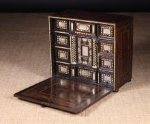 A Late 17th Century Milanese Table Cabinet clad in rosewood & ebony veneers inlaid with engraved bone & mother-of-pearl. The fall front opening to reveal a fitted interior housing small drawers surrounding a central cupboard lined in embossed crimson velvet. The façades elaborately decorated with chequered bands framing central panels of engraved mother of pearl and fine chequered half column pilasters to the centre. 17¾ ins (45 cms) high, 10¾ ins (50 cms) wide, 10¼ ins (26 cms) deep.