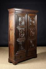 An 18th Century & Later French Armoire/Cupboard. The two long doors having three moulded panels decorated with turned roundels, carved half flower heads and foliate sprays, above two shallow base drawers on bracket feet, 71 ins (180 cms) in height, 42 ins (107 cms) wide, 14 ins (35.5 cms) deep.