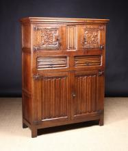 A Flemish Gothic Oak Cupboard. The moulded cornice above two upper cupboard doors hung on decorative strap hinges and carved with entwined foliate stems bearing clusters of berries spewn forth from the mouths of small mythical creatures. The doors flanking a central linen fold panel, above two frieze drawers carved with horizontal linen folds, and two base cupboard doors of vertically carved folds. Standing on stile supports, 60 ins (152 cms) high, 46 ins (117 cms) wide, 17 ins (43 cms) deep.