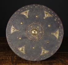A Scottish Highlander's Leather-clad Wooden Targe or Sheild, decorated with brass studs and bosses, 18¾ ins (48 cms) in diameter.