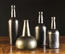 Four Glass Bottles: A late 17th century onion bottle 8 ins (20 cms) in height, and three 18th century bottles 12 ins  (30 cms), 9½ ins (24 cms) and 8¼ ins (21 cms) in height.