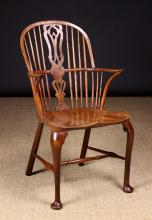 A Yew-wood High hoop-backed Windsor Armchair. The shaped & fretted central back splat flanked by four long spindles either side with three further underarm spindles and bent-wood end supports.  The elm seat with scribed edging line, on cabriole legs united by a turned H-stretcher and terminating on pad feet, 39 ins (100 cms) high, 22 ins (56 cms) wide.