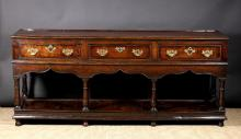 A Fine 18th Century Montgomeryshire Oak Pot Board Dresser. The ogee arched apron edged in moulding and housing three cock-beaded  frieze drawers with mahogany banded borders raised on four baluster turned front legs with two turned and two plain inner rear legs leading down to the pot board base terminating on turned feet. , 34¼ ins (87 cms) in height, 80¼ ins (204 cms) in length, 20½ ins (52 cms) wide.