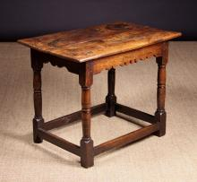 A Late 17th Century Welsh Oak Side Table. The planked top above a shaped apron rail on turned legs united by peripheral stretchers, 25 ins (64 cms) high, 31 ins x 20½ ins (79 cm x 52 cms).