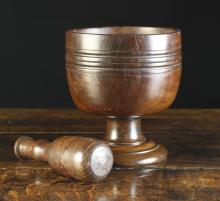 A Good 19th Century Turned Lignum Vitae Pestle & Mortar. The goblet form mortar with ring-turned decoration, 8 ins (20 cms) high, 7½ ins (19 cms) in diameter. The pestle 8 ins (20 cms) in length.