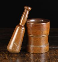 An Early 19th Century Turned Treen Pestle & Mortar. The mortar 6¼ ins (16 cms) high, the pestle 9½ ins (24 cms) in length.