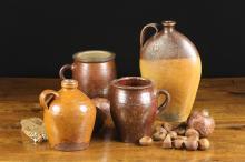 Four Glazed Terracotta Jars: A flattened ovoid flagon 11½ ins (29 cms) in height, a bulbous flagon with side handle 6¾ ins (17 cms) high, a salt glazed jar with flanged rim and side handle 6 ins (15 cms) high, and another jar 7 ins (18 cms) high.