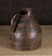 A Large 19th Century Coopered Iron Bound Oak Jug, 14 ins (36 cms) in height.