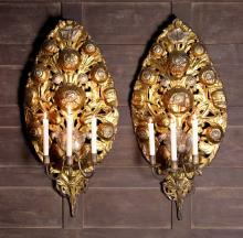 A Pair of Late 17th Century Silvered & Gilt Repoussé Wall Sconces. Each sconce having three scroll branches emanating from a pierced oval sheet metal wall mount embossed with flowers and foliage, 35 ins x 16½ ins (89 cm x 42 cms).