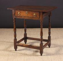 A Diminutive 18th Century Oak Side Table.  The rectangular top having a moulded edge above a single frieze drawer incised with edging lines and fitted with brass ring handles. Standing on slender acorn-knopped baluster turned legs united by peripheral stretchers and terminating on turned feet, 25 ins (63 cms) high, 24½ ins (62 cms) wide, 14½ ins (37 cms) deep.