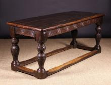 A 17th Century & Later Oak Refectory Table. The thick planked top with cleated ends and rounded corners above a carved frieze of leafy C-scrolls enriched with punch-work. Standing on bold ball-knopped baluster legs with possibly later carved flowering plants above rounded block feet united by low peripheral block stretchers, 30¾ ins (79 cms) high, 72 ins (183 cms) in length, 30 ins (76 cms) wide.