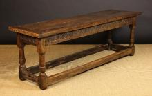 A 17th Century Oak Refectory Table (A/F).  The planked top with cleated ends on foliate carved frieze rails and columnar legs with cup turning above square block feet united by peripheral block stretchers, 29 ins (74 cms) high, 84 ins (213 cms) long, 25 ins (64 cms) wide.