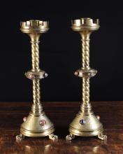 A Pair of Fine 19th Century Neo-Gothic brass Candlesticks. The candle sockets in crenulated drip pans above barley twist columns with annular centre knops and conical bases enriched with engraved scrollwork and studded with agate cabochons, standing on three lion paw feet, 18 ins (46 cms) in height.