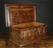 A Fine 16th Century North Italian Cedar Box with pyrographic decoration.  The rectangular lid on wire loop hinges opening to reveal a fine encampment scene emblazoned to the lid interior, with a box compartment to one end embellished with flowers and foliage. The front board depicting figures, arcading and two galleons silhouetted against a cut away punchwork 'mesh' ground, standing on a moulded base, 10 ins (25 cms) high, 26¾ ins (68 cms) wide, 14 ins (36 cms) deep.