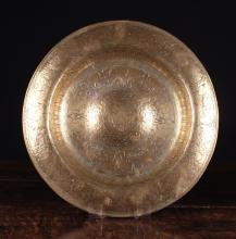 A Late 16th Century Italian Brass Alms Dish decorated with elaborate engraving, 16 ins (41 cms) in diameter.