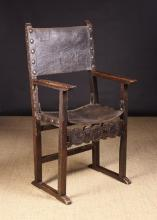 A Late 17th/ Early 18th Century Spanish Walnut Armchair. The tooled leather back and seat edged in brass studs. 51.5 ins (128 cm) tall.